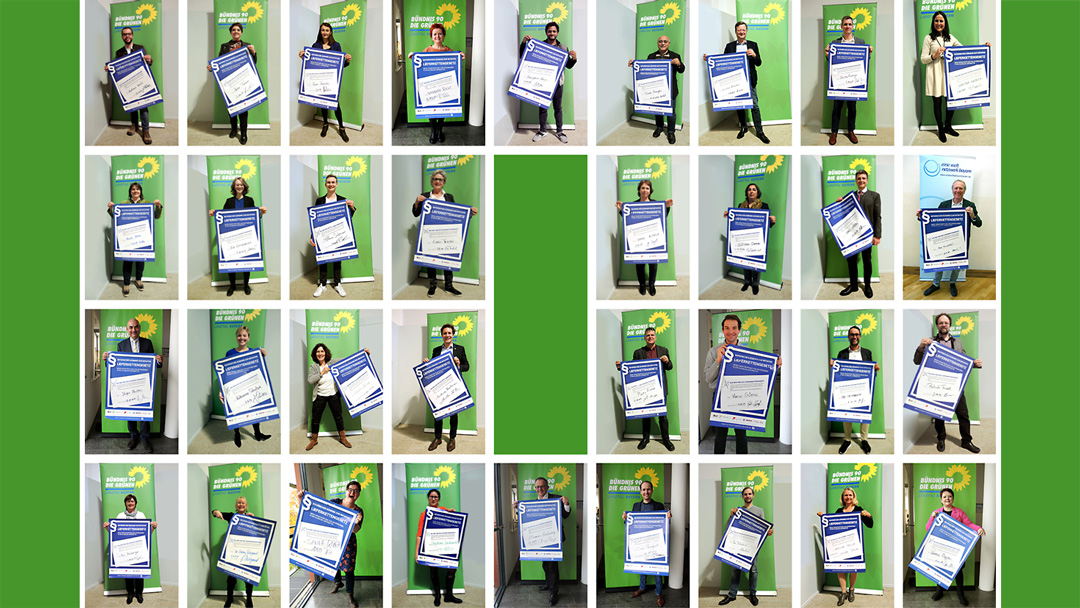 Foto mit Abgeordeneten, die unterzeichnetes Lieferkettengesetz-Plakat präsentieren
